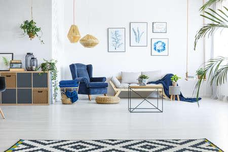 Ruime woonkamer met sofa, fauteuil en posters