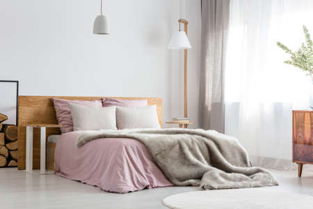 Fluffy grey blanket on wooden bed with pink bedding Standard-Bild