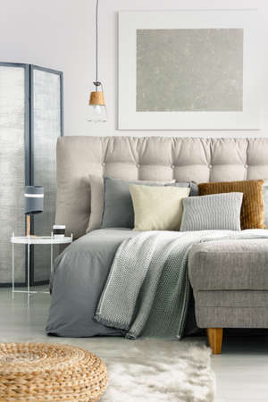 Grey blanket and pillows on comfortable bed in spacious bedroom