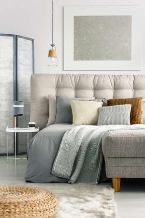 Grijze deken en hoofdkussens op comfortabel bed in ruime slaapkamer