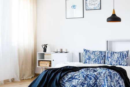 Navy blue blanket on white bed in stylish bedroom