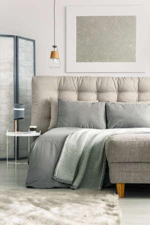 편안한 침대와 오토만이있는 회색 아늑한 침실