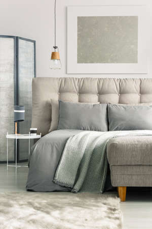 Grey cozy bedroom with comfortable bed and ottoman