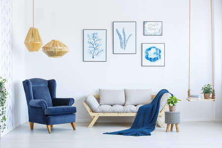 White sofa and blue armchair in living room with posters on the wall