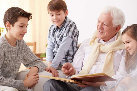 Lovely grandfather showing family photos to his beautiful grandchildren Stock Photo