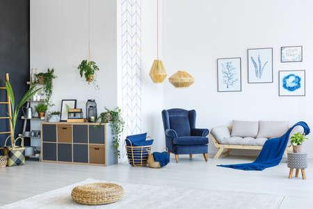 植物やポスターでモダンな白と青のリビング ルーム