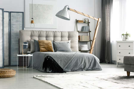 Grey screen by the bed in cozy spacious bedroom