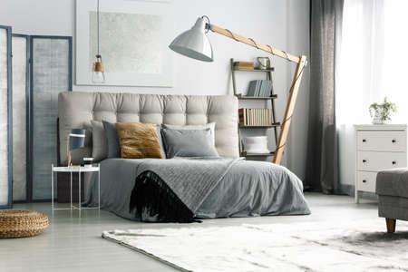 Grijs scherm bij het bed in gezellige ruime slaapkamer