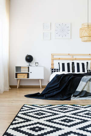 nightstand: Carpet with black and white pattern in cozy modern bedroom Stock Photo