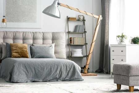 Wooden decor in cozy grey bedroom with shelf made of ladder