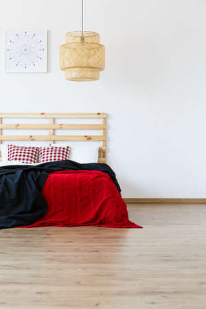 Wooden bed with red and black blankets in spacious bedroom