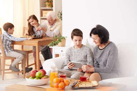 少年と現代タブレットを使用して美しい祖母