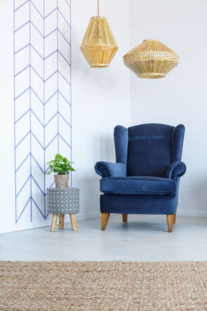 Stylish blue armchair in white living room