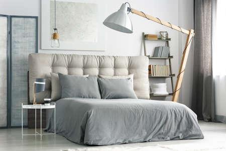 회색 침구 편안한 침대 근처에 큰 나무 램프 스톡 콘텐츠