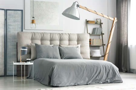 Big wooden lamp near comfortable bed with grey bedding