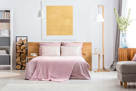 Natural decor of cozy white and pink bedroom with wooden additions