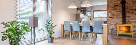 Sala da pranzo spaziosa con grande tavolo e camino in metallo Archivio Fotografico - 81889362