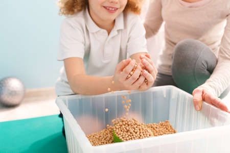 Garçon jouant avec des pois chiches pendant sa thérapie d'intégration sensorielle Banque d'images - 81928410