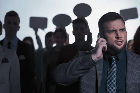 Angry man talking on phone, crowd in background