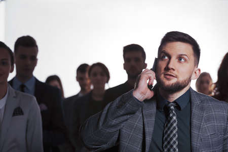 Busy man talking on phone, crowd in background