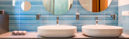 sinks: Two sinks and mirrors in a blue bathroom