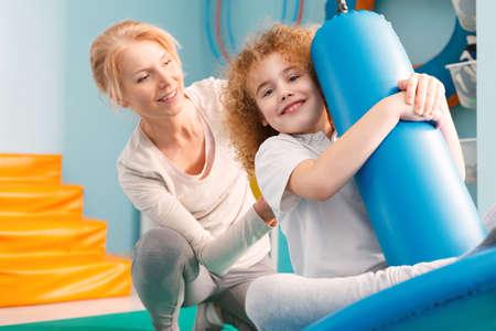 Terapeuta sonriente que mira a un muchacho en oscilación del disco durante la sesión de terapia