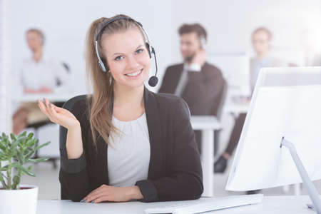 Pretty call center worker working in modern office Imagens