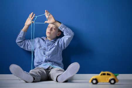 Jongenszitting op een vloer en spelend met een kabel en een stuk speelgoed auto