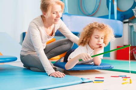 Focused kid having sensory integration session with professional therapist