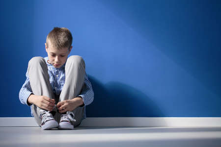 Depressed boy sitting on a floor in blue room Imagens