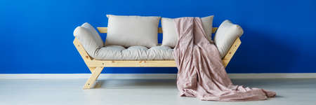 Pastel pink blanket on modern, wooden sofa Stock Photo