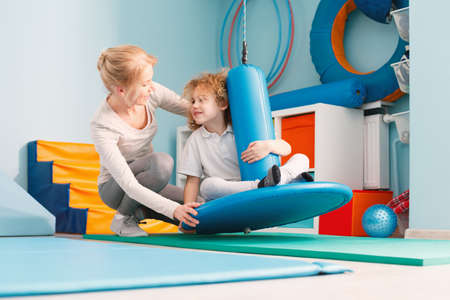 Boy using sensory integration equipment and a woman helping him
