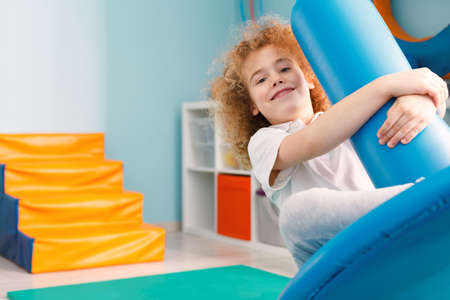 Happy boy using blue disc swing for therapy Фото со стока