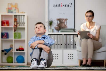 Jonge psycholoog praten met depressieve jongen in haar kantoor