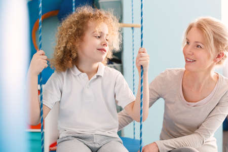 Boy sitting on a swing and talking to physiotherapist Stock Photo