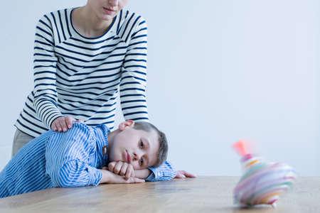 Droevige jongen en zijn moeder kijken naar spinnende bovenkant op houten tafel