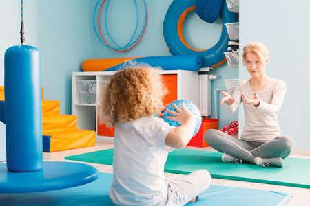 Junge spielt mit seinem Therapeuten mit einem Ball