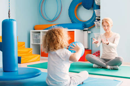Boy playing with his therapist using a ball