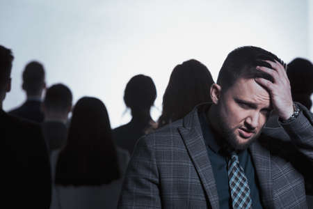 Exhausted man standing in anonymous crowd of people