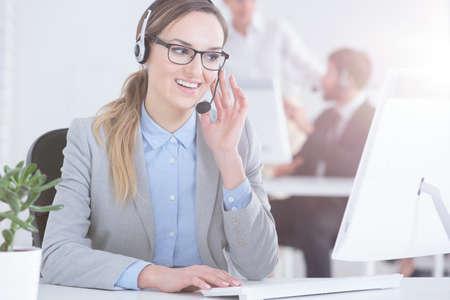 Mooie call centrewerker die op het werk in bureau wordt geconcentreerd Stockfoto