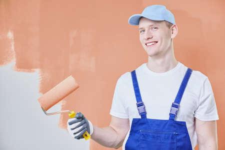 Professionele schilder die een rol houdt en tegen oranje muur staat Stockfoto - 82013616