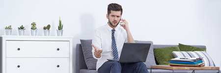 Man working at home using laptop and mobile phone