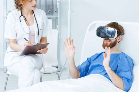 Young male patient in VR talking to young female doctor Stock Photo