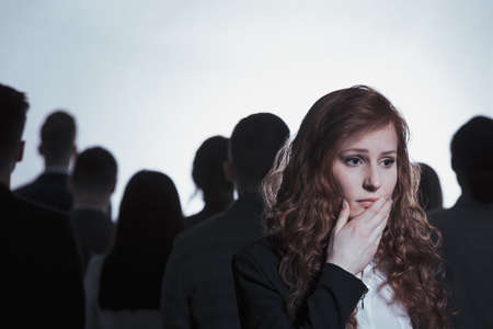 Worried woman standing in crowd of people