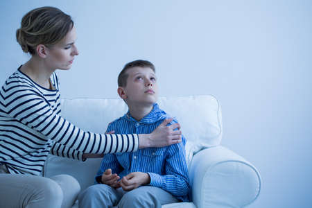 Mother and her autistic son sitting on the sofa Banco de Imagens