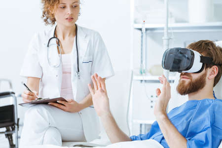 Focused young female doctor watching male gesticulating patient in VR Imagens