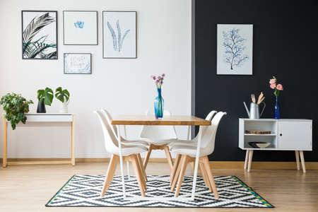 黒と白のカーペットの上に立って花を持つ木製のテーブル
