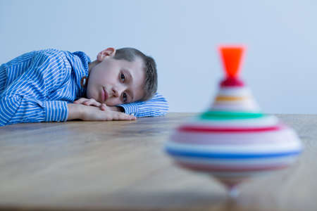 Sad boy and spinning top on wooden table