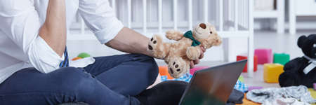 pedant: Man sitting in front of laptop screen and holding teddy bear Stock Photo