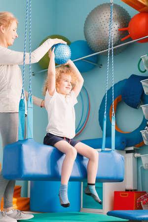 Niño sentado en un columpio y haciendo ejercicio con una pelota durante la sesión de integración sensorial